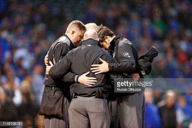 Umpires Chad Whitson Lance Barksdale Ted Barrett and umpire John Tumpane gather at the home plate before the start of a game between the Chicago Cubs...