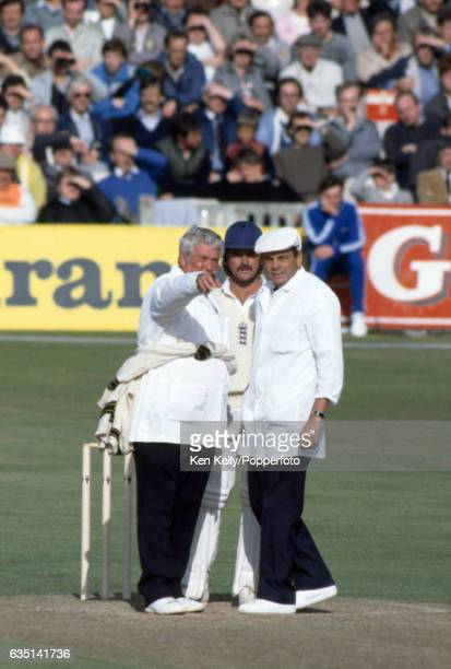 Umpires David Shepherd and Dickie Bird with England batsman Allan Lamb look for the source of reflected light in the stands that had stopped play...