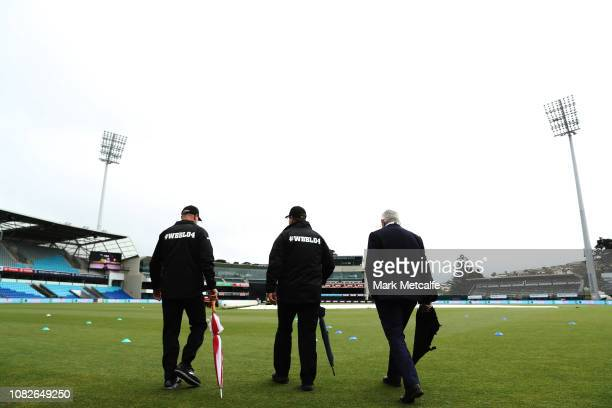 Umpires inspect the pitch before the Women's Big Bash League match between the Sydney Thunder and the Adelaide Strikers at Blundstone Arena on...