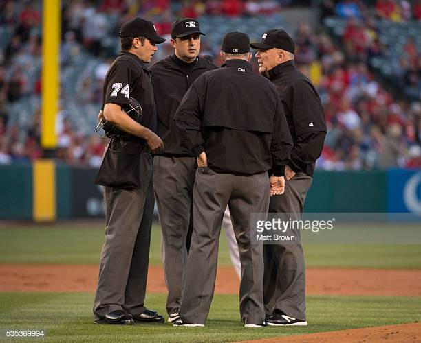Umpires John Tumpane Lance Barrett Dale Scott and Bob Davidson discuss a fan interference call during the first inning of the game between the...