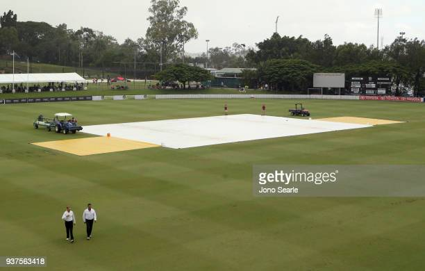 Umpires leave the ground as covers remain during a rain delay during day three of the Sheffield Shield final match between Queensland and Tasmania at...