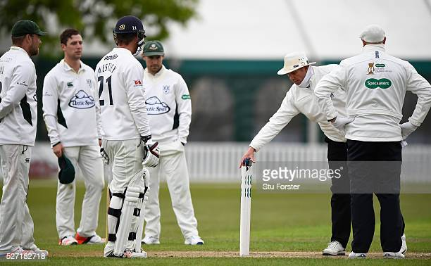 Umpires Neil Mallender and Michael Burns discuss the light during day two of the Specsavers County Championship Division Two match between...