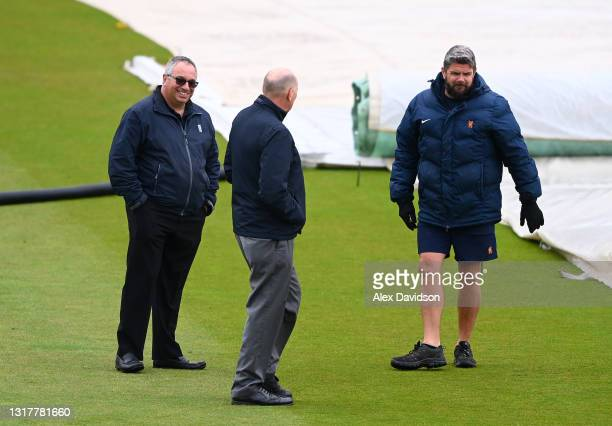 Umpires Neil Mallender and Neil Bainton speak to Lord's Head Groundsman Karl McDermott as they inspect the outfield as play is delayed due to rain on...