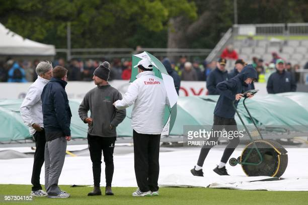 Umpires Nigel long and Richard Illingworth check the pitch as groundsmen work on the wet pitch at Malahide cricket club in Dublin as the start of...
