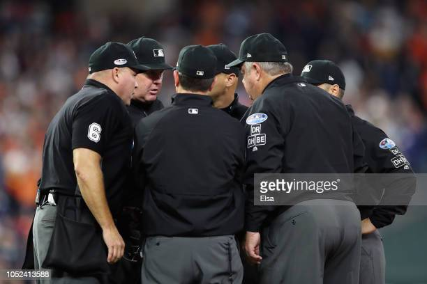 Umpires review a fan interference call in the first inning during Game Four of the American League Championship Series between the Boston Red Sox and...