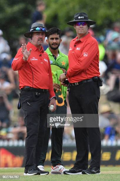 Umpires Richard Illingworth and Chris Brown look on as rain delays play during the second match in the One Day International series between New...