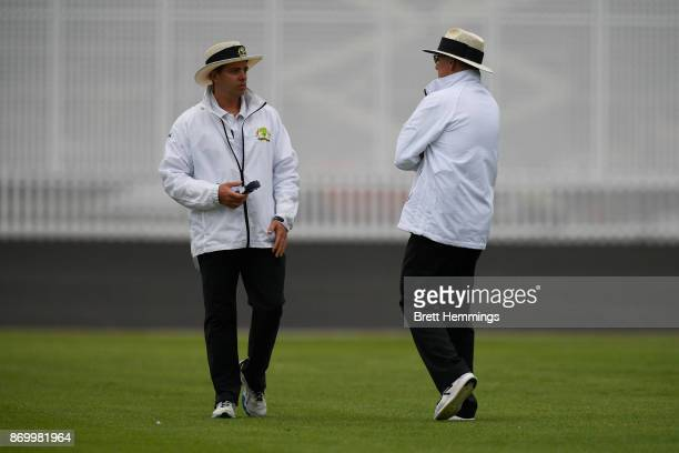 Umpires Shawn Craig and Bruce Oxenford signal a break an play due to poor light during day one of the Sheffield Shield match between New South Wales...