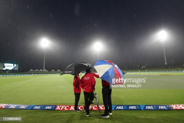 Umpires stand on the boundary as rain forces a delay in play during the third Twenty20 International cricket match between New Zealand and the West...