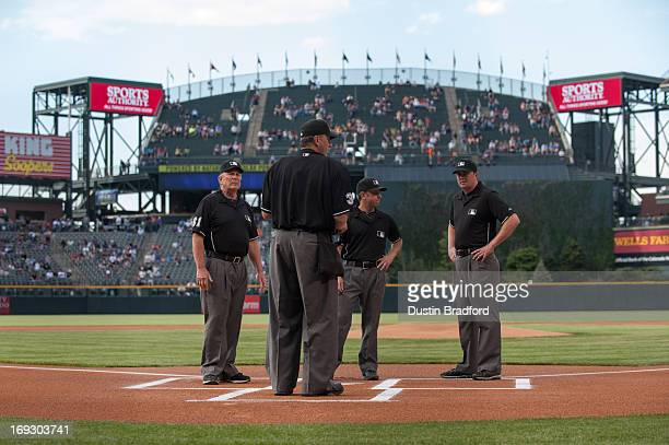 Umpires Tim McClelland Lance Barrett Chris Guccione and Bob Davidson meet at home plate before a game between the Colorado Rockies and the San...