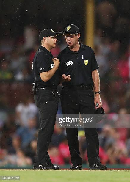 Umpires Tony Wilds and Shawn Craig speak during the Big Bash League match between the Sydney Sixers and the Melbourne Renegades at Sydney Cricket...