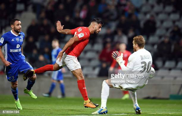 Umut Bozok of Nimes scores his second goal and Gaetan Deneuve of Bourg en Bresse during the Ligue 2 match between Nimes and Bourg en Bresse at Stade...