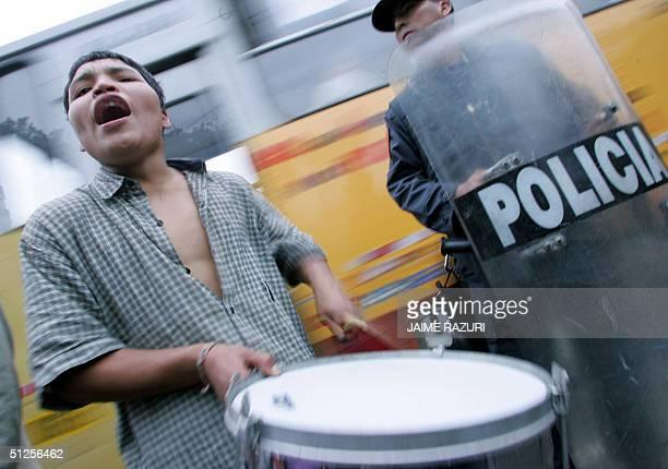 Un adolescente trabajador protesta al lado de un policia antimotines el 02 de setiembre de 2004 frente al Congreso peruano contra un proyecto de ley...