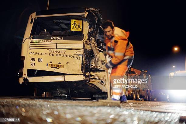Un agent communal balaie autour d'un car scolaire accidenté après une collision avec un TER à un passage à niveau le 14 décembre 2010 à Jonches...
