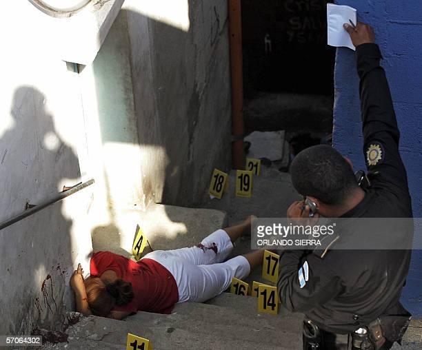 Un agente de la Policia Nacional Civil observa el cadaver de una mujer que permanece sin vida sobre unas gradas en las inmediaciones del estadio...
