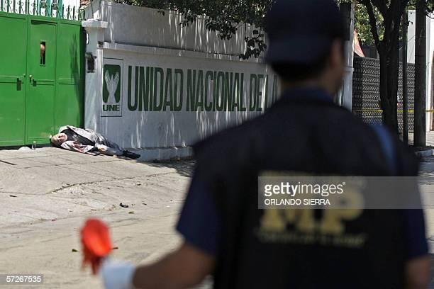 Un agente del Ministerio Publico observa la escena del crimen donde permanece el cadaver del diputado Mario Pivaral asesinado en la puerta de la sede...