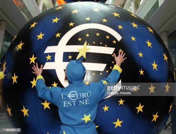 Un artiste habillé aux couleurs de l'euro pousse une boule géante, le 04 janvier au siège de la banque Paribas à Paris, à l'issue de la parade des...