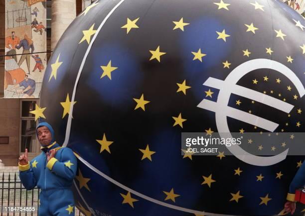 Un artiste habillé aux couleurs de l'euro tire une boule géante, le 04 janvier de la Madeleine à la place du marché Saint-Honoré à Paris, lors de la...