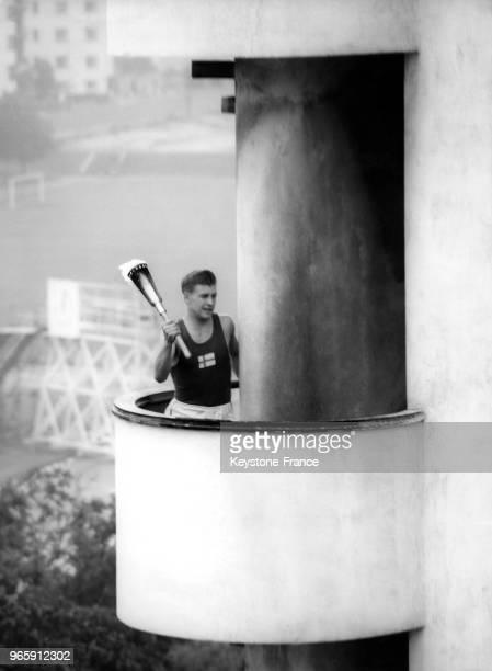 Un athlète finlandais porte la flamme olympique sur la tour du stade lors de la cérémonie d'ouverture des JO le 19 juillet 1952 à Helsinki, Finlande.