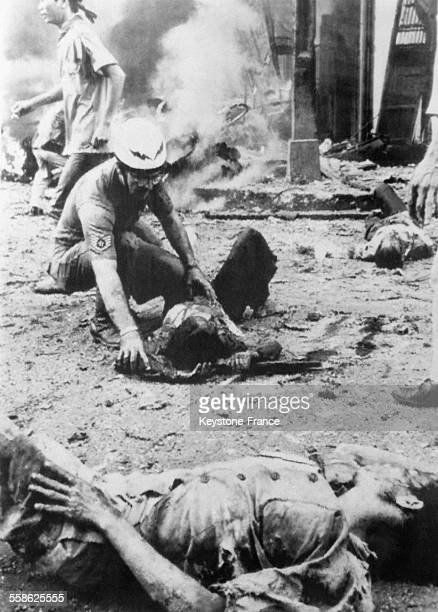 Un attentat Vietcong a l'ambassade des EtatsUnis cause la mort de 160 personnes vietnamiens et americains ici une femme blesse recoit l'aide d'un...