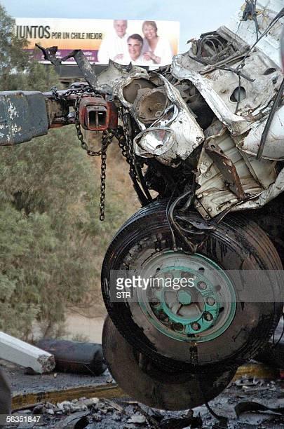 Un cartel de propaganda electoral puede verse detras de los restos de un autobus que se accidento dejando hasta ahora cinco muertos y una veintena de...