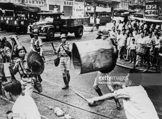 Un Chinois lançant une poubelle sur les policiers dans les rues de Hong Kong en juin 1967
