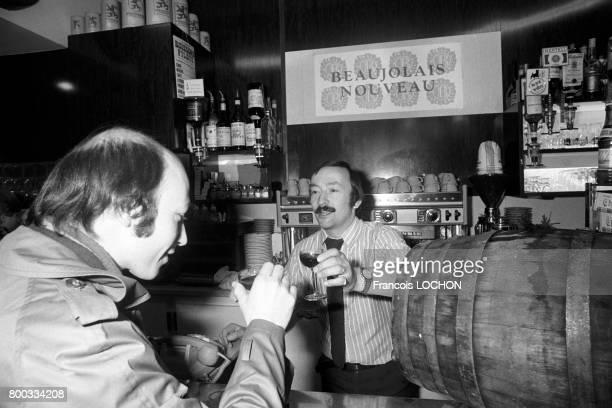 Un client s'apprête à goûter le Beaujolais nouveau dans un bar en novembre 1975 à Paris France