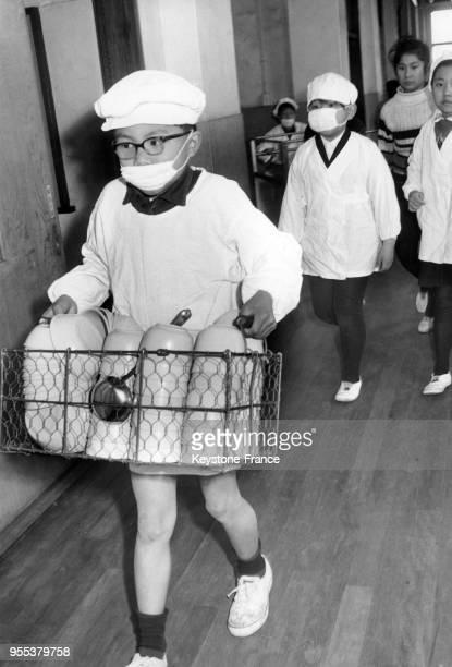 Un écolier masque sur le visage porte les couverts pour le déjeuner dans une classe à Tokyo Japon
