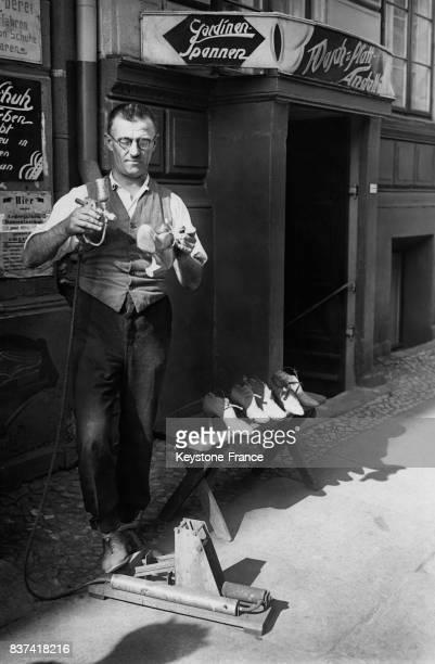 Un cordonnier reteinte les chaussures à l'aide d'une machine dans la rue circa 1920 en Allemagne