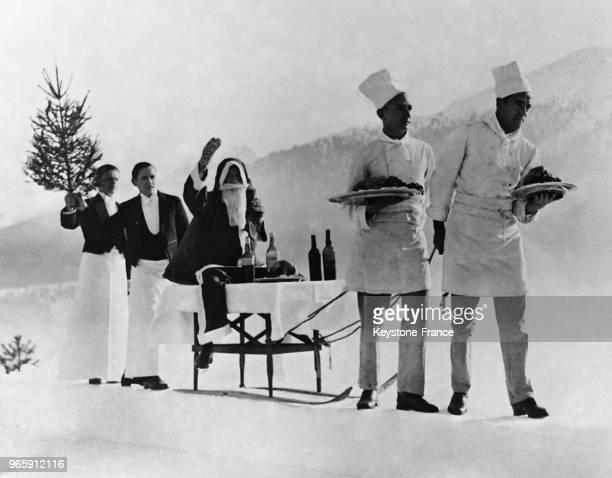 Un cortège formé par deux cuisiniers et deux garçons de café escortant le Père Noël à son arrivée à SaintMoritz Suisse le 25 décembre 1932