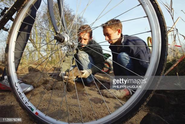 Un cycliste passe devant des élèves du lycée horticole de Raismes qui rénovent le 20 novembre 2002 à Walllers le secteur pavé emprunté par course...