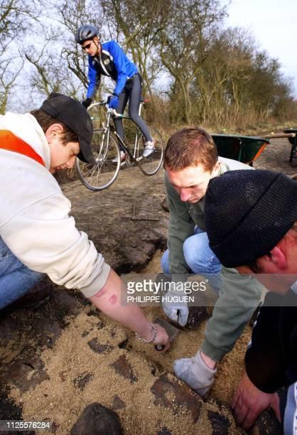 Un cycliste passe près d'élèves du lycée horticole de Raismes qui rénovent le 20 novembre 2002 à Walllers le secteur pavé emprunté par course...