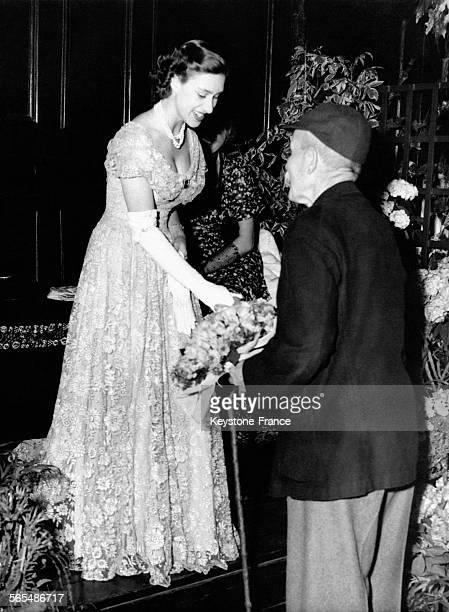 Un danseur de la troupe Morris remet un bouquet de fleurs à la Princesse Margaret après une démonstration de danse le 22 juin 1949 à Londres...