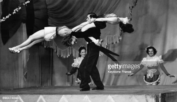 Un danseur fait tournoyer deux danseuses sur ses épaules aux FoliesBergères le 21 avril 1940 à Paris en France