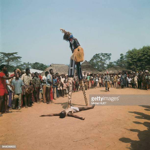 Un danseur yacouba porte le masque à échasses Gle gben en Côte d'Ivoire vers 19501960 Le danseur porte une cagoule en filet noir une haute coiffure...