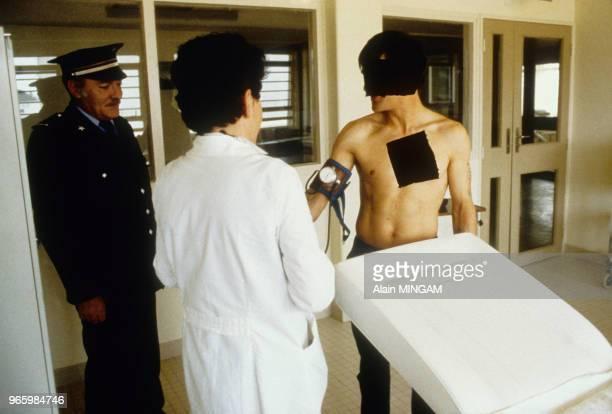 Un détenu accompagné d'un gardien consulte un médecin à l'infirmerie de la maison d'arrêt de Lorient le 17 mars 1983 Ploemeur France