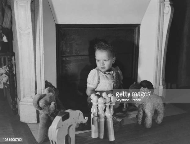 Un enfant assis devant la cheminée entouré des jouets reçus à Noël en décembre 1947 en France