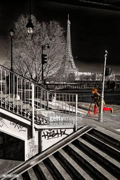 Un enfant au pantalon rouge approchant en trottinette des escaliers du Pont de BirHakeim 16 février 2016 à Paris France