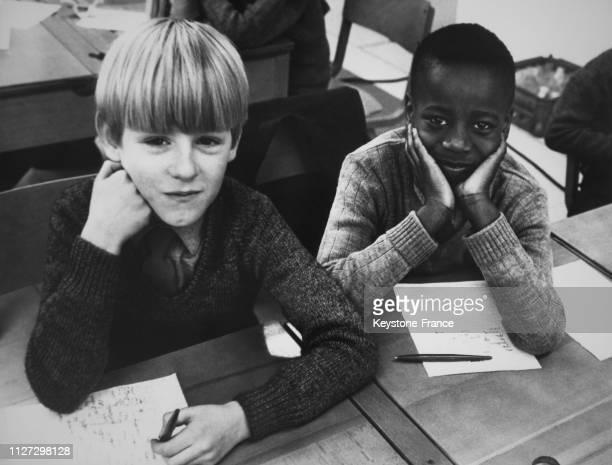 Un enfant blanc et un enfant noir assis côte à côte à l'école de Wolverhampton RoyaumeUni le 8 mars 1968