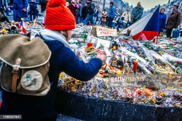 """Un enfant dépose des fleurs sur le mausolée de Yan Pallasch, place Venceslas lors de la """"Révolution de Velours"""", le 27 novembre 1989 à Prague,..."""