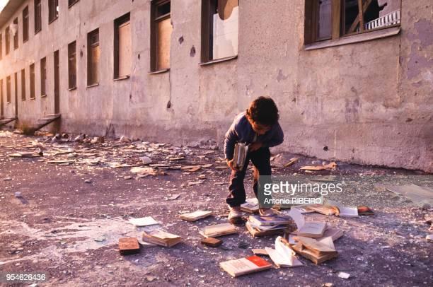 Un enfant ramasse des livres dans une rue de Tbilissi lors de la guerre civile en Géorgie en septembre 1991.