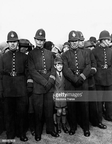 Un enfant s'est faufilé entre les policiers pour être bien placé pour voir passer la procession à Trafalgar square Londres Angleterre RoyaumeUni le...