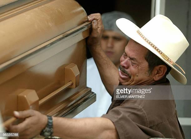 Un familiar de un recluso muerto la vispera llora cuando sale de la morgue con uno de los feretros, en Tegucigalpa el 6 de enero de 2006. Trece...