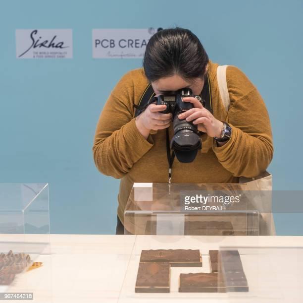 Un femme photographie une réalisation culinaire exposée au 30 ème Salon International de la Restauration de l'Hotelerie et de l'Alimentation à...