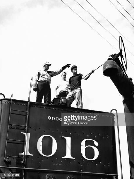 Un formateur avec deux jeunes apprentis cheminots sur une locomotive à vapeur s'activant pour remplir d'eau la cuve, le 25 juin 1944, à Carbondale,...