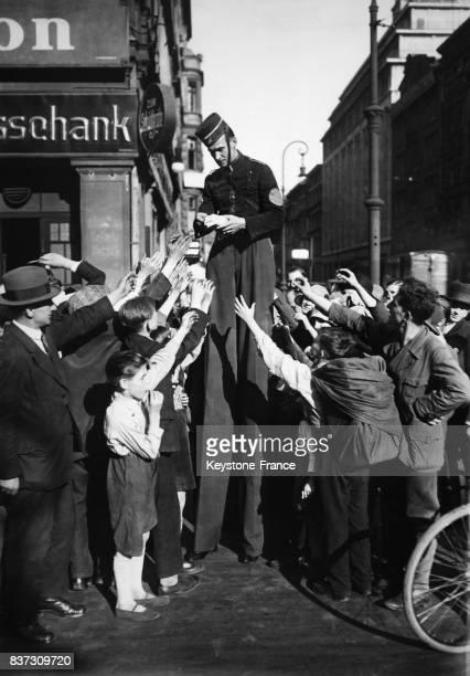 Un 'géant' monté sur des échasses distribue des tracts publicitaires pour une marque de chaussures aux passants enthousiasmés à Berlin Allemagne