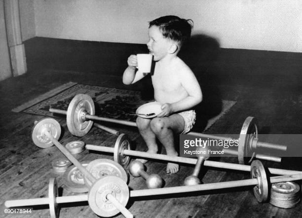 Un garçon de 4 ans, fils d'une haltérophile britannique, boit un verre de lait après sa séance d'haltérophilie le 13 novembre 1959 à Liverpool,...