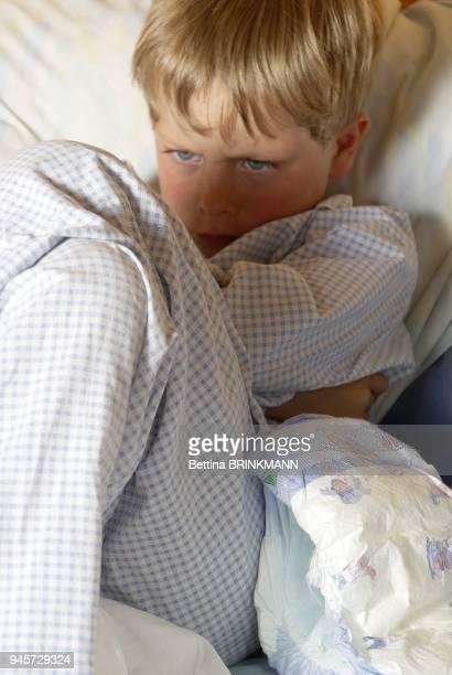 Un garon de 6 ans est assis dans son lit en train de bouder une couche est pose ct de lui