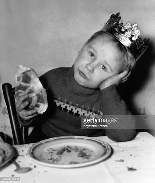 Un garçon de quatre ans l'air songeur devant son assiette vide après avoir célébré l'Epiphanie le 3 janvier 1958