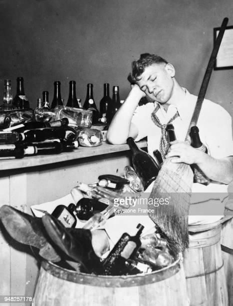 Un garçon d'un bar affalé sur une chaise et les pieds dans une poubelle remplie de bouteilles vides après avoir célébré la fin de la prohibition à...