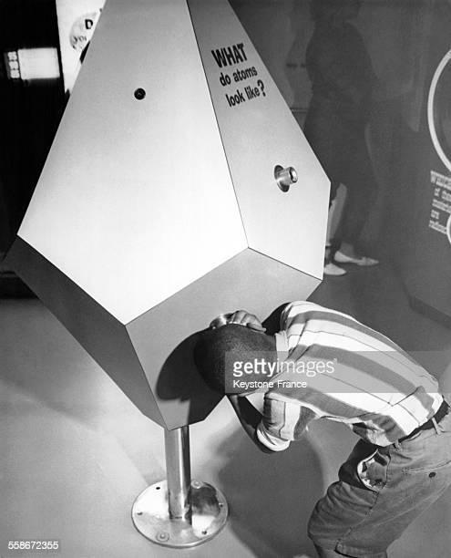 Un garçon se penche afin de regarder à l'intérieur d'une activité proposant de découvrir comment se présente la matière atomique de l'intérieur